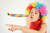 Young beauty woman in clown wig and party blower pointing left, — Stock Photo