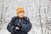 Boy keeps in hands snowball in wood in winter, looking aside — Stock Photo