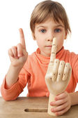 Pretty little girl is played by wooden hand of manikin isolated — Stock Photo