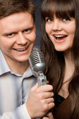 Young beautiful woman and smiling man sing in microphone — Stock Photo