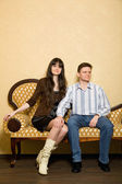 Young beautiful woman and man sitting on sofa in room — Stock Photo