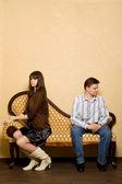 Giovane donna e giovane uomo seduto sul divano in sala — Foto Stock