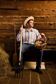 Young man with pitchfork,with basket of fruit and in straw hat — Stock Photo