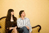 Young woman and young man sitting on sofa in room — Stock Photo