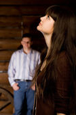 Beautiful woman brunette and young man in wooden log hut — Stock Photo