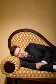 Businessman in suit sleeping on sofa in room — Stock Photo