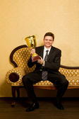 Smiling businessman with win cup in hand in suit sitting on sofa — Stock Photo