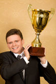 Smiling businessman in suit with win cup in hand — Stock Photo