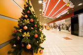 Fur-tree densely covered by Christmas ornaments in shopping cent — Stock Photo