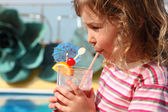 Little girl in shirt with pink stripes drinking cocktail with fr — Stock Photo