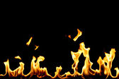 Yellow fire with flame tongues isolated on black — Stock Photo