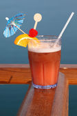 Cocktail with fruits in glass on ship deck rail, sea on backgrou — Stock Photo