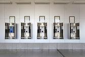 De nombreux téléphones publics dans la grande salle aux murs blancs et granit floo — Photo