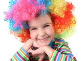 Kleines mädchen in clown perücke, lächelnd und blick in die kamera am kinn — Stockfoto