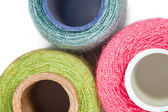 Fragment of three coils with multi-coloured sewing threads isola — Stock Photo