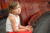 Little girl sitting on stair near armchairs in circus and lookin — Stock Photo