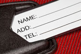 Fragment of label with identification data on red textural fabri — Stock Photo