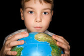 Boy keeps in hands over globe of world isolated on black backgro — Stock Photo