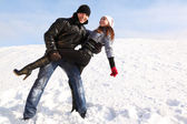 Young man and girl dance on snowy area and smiling, man looking — Stock Photo