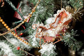Christmas ornaments in form of sledge on artificial fur-tree, br — Stock Photo