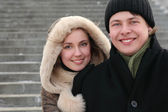 Ceketli adam arkadan kucaklayan ve gülümseyen bir kukuleta ile genç kız — Stok fotoğraf