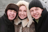 Three friends smiling and looking at camera, half body, winter d — Stock Photo