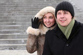 Young girl in coat with hood and man in black dress smiling and — Stock Photo