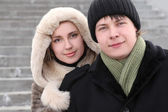 Young girl in coat with hood embracing man from back and smiling — Stock Photo