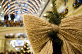 Christmas ornament in form of bow on fur-tree in shopping centre — Stock Photo