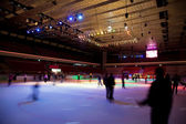 Big covered skating rink with multi-coloured illumination in spo — Stock Photo