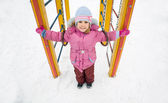 Little pretty smiling girl in pink jacket on playground in winte — Stock Photo