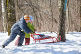 Boy and little girl push sledge in winter in wood — Stock Photo