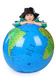 Boy in historical dress leans on inflatable globe chin on hands — Stock Photo