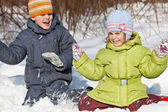 Boy and little girl play sitting in snow in winter in wood — Stock Photo