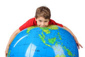 Boy in red shirt lies on inflatable globe isolated on white back — Stock Photo