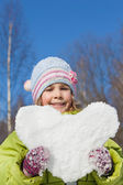 Smiling little girl keeps in hands hearts from snow in winter in — Stock Photo