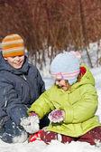 Junge und Mädchen spielen in sonnigen Tag im Winter im Schnee sitzen — Stockfoto