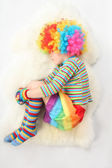Boy in clown dress sleeping view frome above on white background — Stock Photo