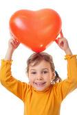 Roześmiany dziewczynka posiada ponad jej głową serca kształt balonu iso — Zdjęcie stockowe