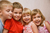 Laughing children four together in cosy room, two pretty girls a — Stock Photo