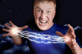 Aggressive man allows lightnings from hands in nightly sky, coll — Stock Photo