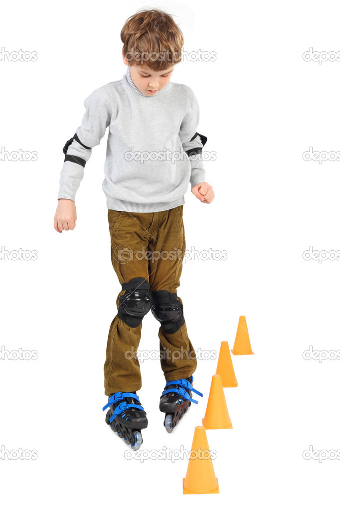 Little boy rollerblading near orange cones looking down isolated on white — Photo #7936806
