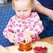 Adorable toddler girl helping at kitchen - Stock Photo