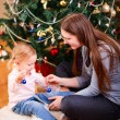 Mother and daughter near Christmas tree — Stock Photo #7498292