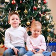 Two kids near Christmas tree — Stockfoto #7498300