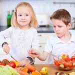 Two little kids making salad — Stock Photo