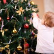 Little girl decorating Christmas tree — Foto Stock