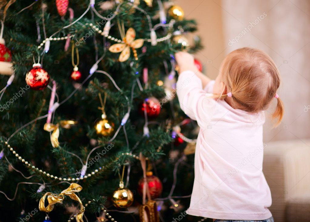 Back view of toddler girl decorating Christmas tree — Zdjęcie stockowe #7907007