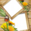 Photo frame on a wooden background with butterflies and flowers — Stock Photo