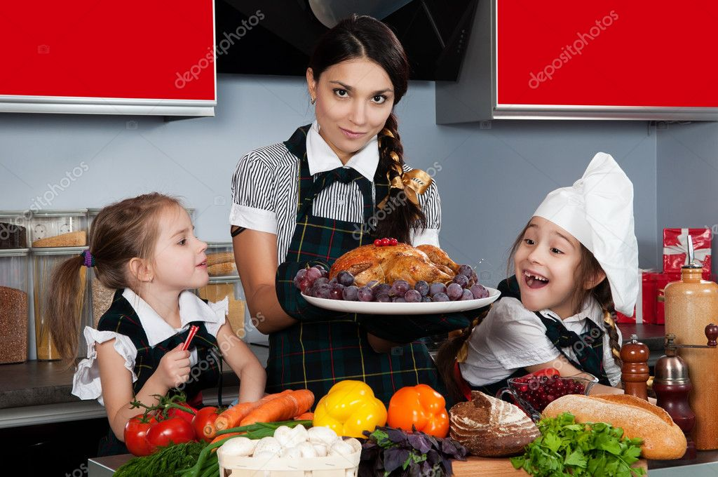 Mother with two daughters in the kitchen preparing Christmas dinner with turkey and vegetables — Stock Photo #7521263